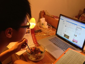 Pengfei Shi checking his RenRen account while enjoying his dinner